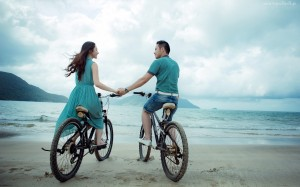 イメージtwo_lovers_riding_bicycle_on_the_beach-wide